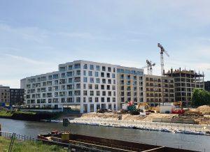 Das Ensemble BUWOG THE ONE liegt direkt am Berlin-Spandauer-Schifffahrtskanal, rechts im Bild der Baufortschritt der Uferanlage. Foto: BUWOG / Divé