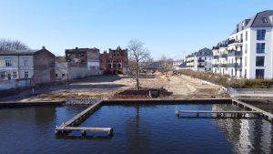 """Grundstück am Wasser: Auf der leeren Fläche entsteht bald BUWOG HELLING HOF. Rechts daneben: Das Ankerviertel, eine Kita und das """"Haus an der Dahme"""" - bereits 2020 fertiggestellt. Foto: BUWOG"""
